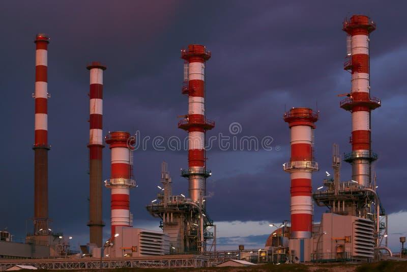 Peça de muitas chaminés de uma refinaria de petróleo na noite imagem de stock royalty free
