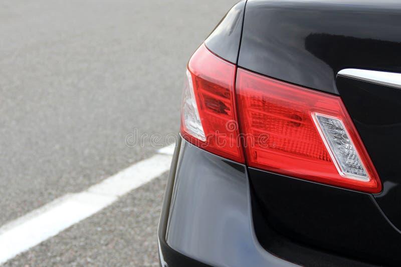 Peça de um carro preto no fundo do asfalto Headlig luxuoso fotografia de stock