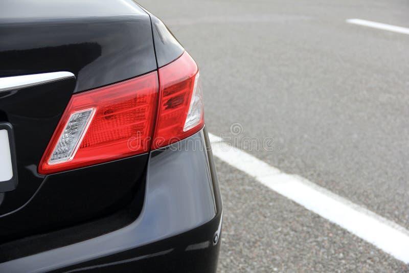 Peça de um carro preto no fundo do asfalto Headlig luxuoso imagem de stock royalty free