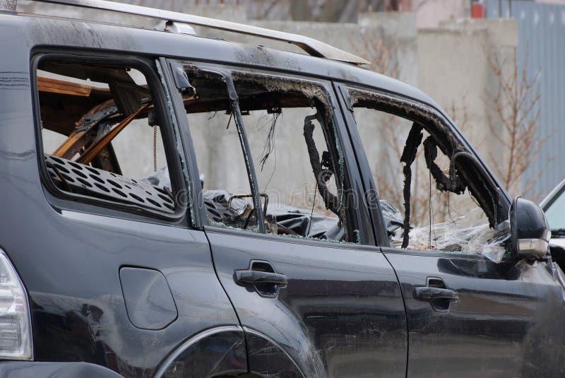 Peça de um carro quebrado preto com as janelas quebradas na rua fotos de stock royalty free