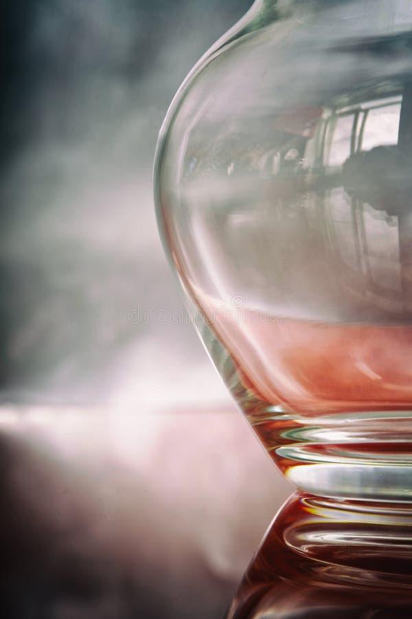 Peça de um jarro de vidro transparente em uma prata e em um fundo cor-de-rosa imagem de stock royalty free