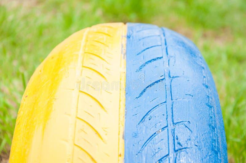 Peça de um pneu de borracha do automóvel Pintado em amarelo e em azul foto de stock royalty free