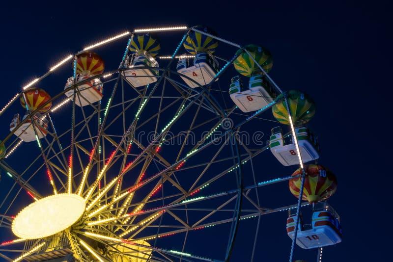 Peça de uma roda de Ferris na noite com cores em mudança foto de stock royalty free