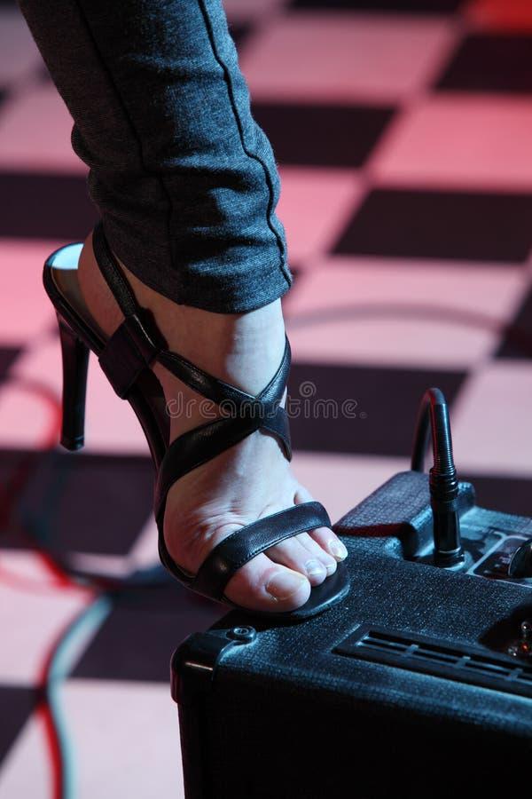 A peça do pé da mulher pisou no amplificador foto de stock
