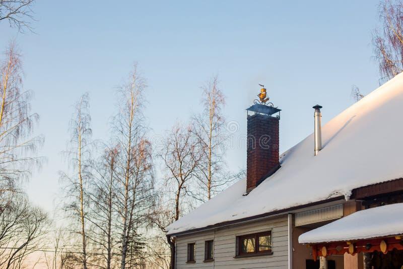 Peça do telhado coberto de neve da casa com a chaminé de que há fumo fotos de stock