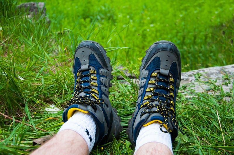 Peça dos pés do homem Em botas trekking azuis Na grama verde foto de stock
