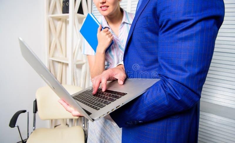 Peça a opinião do colega Internet surfando do portátil da posse do homem de negócios com colega Mostra do sócio comercial do escr fotos de stock royalty free