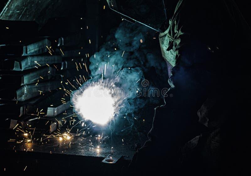 Peças de metal das soldas do soldador, lotes do fumo e faíscas, nocividade, trabalhador imagem de stock