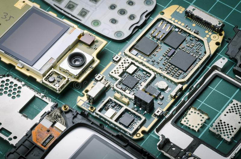Peças eletrônicas do telefone celular velho com close-up das peças do semicondutor e dos metais preciosos no fundo verde foto de stock royalty free