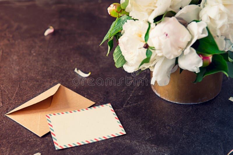 A peônia branca floresce o ramalhete, o cartão vazio e o envelope de papel do ofício no fundo da pedra do preto escuro Vintage qu fotos de stock royalty free