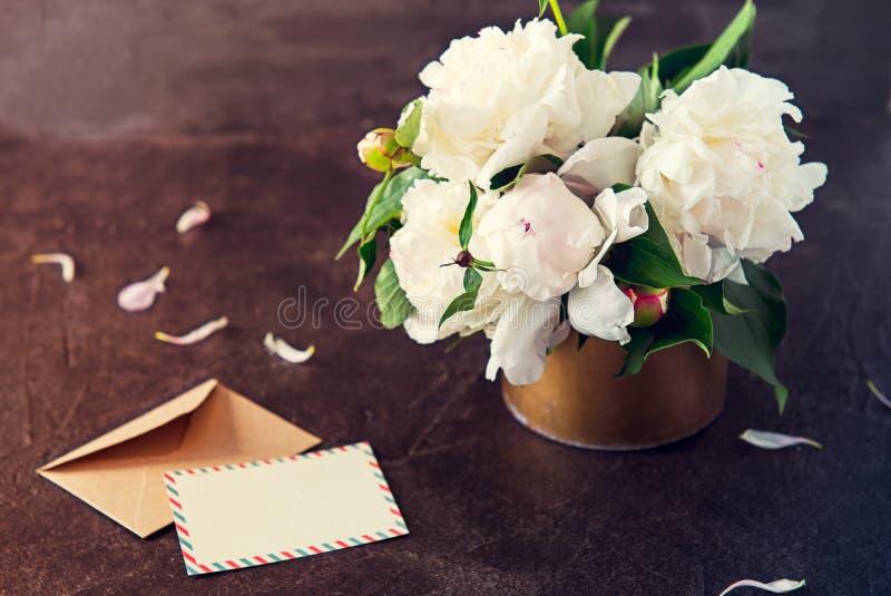 A peônia branca floresce o ramalhete, o cartão vazio e o envelope de papel do ofício no fundo da pedra do preto escuro Vintage qu foto de stock