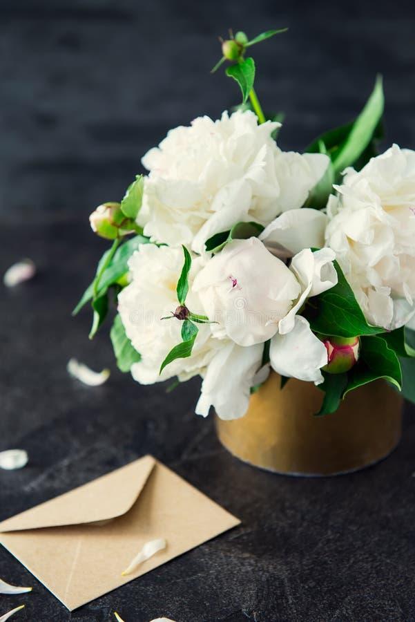 A peônia branca floresce o ramalhete, o cartão vazio e o envelope de papel do ofício no fundo da pedra do preto escuro Zombaria v imagens de stock