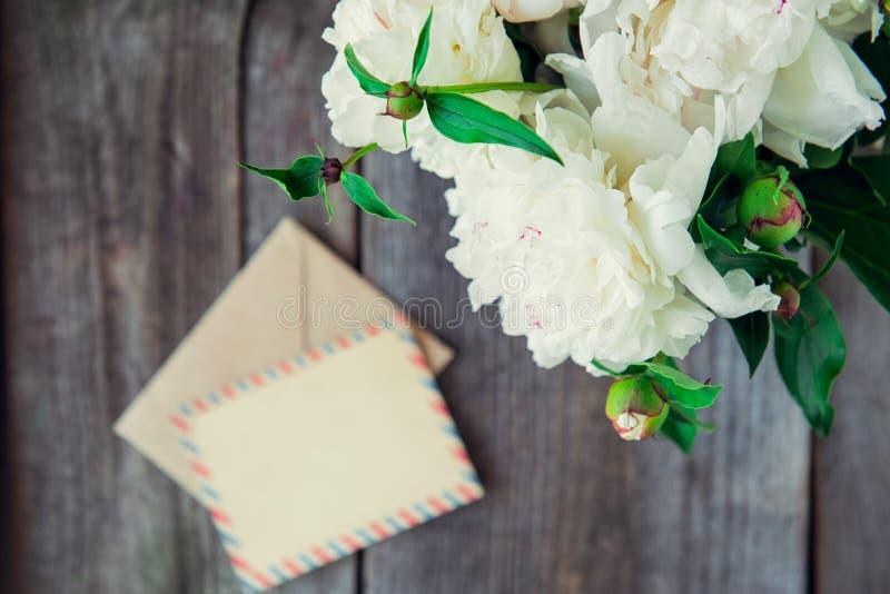 A peônia branca focalizada floresce o ramalhete e o envelope de papel vazio borrado do cartão e do ofício no backgr rústico de ma fotos de stock royalty free