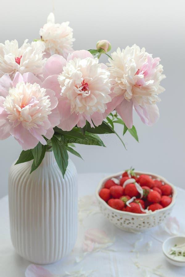 Peônias cor-de-rosa em um vaso branco e em uma bacia de morangos no fundo imagens de stock royalty free