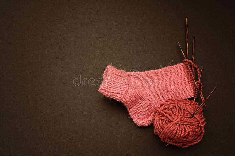 Peúga cor-de-rosa feita malha no fundo preto imagem de stock