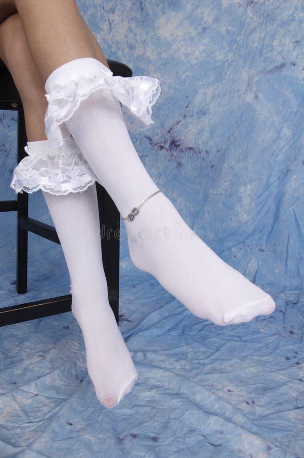 Peúgas brancas da menina e corrente de prata do tornozelo foto de stock