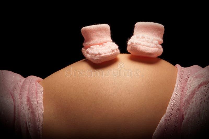 Peúgas cor-de-rosa na barriga grávida fotografia de stock