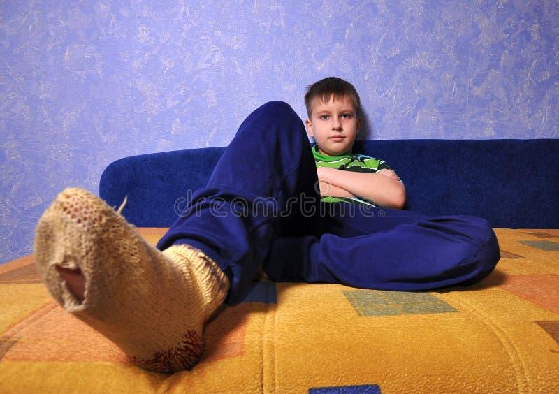 Peúgas desgastando do menino com furos neles fotos de stock royalty free