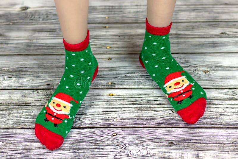Peúgas do bebê do Natal, feriado feliz Ano novo e Feliz Natal Pés do bebê em peúgas vermelhas e verdes com foto de stock
