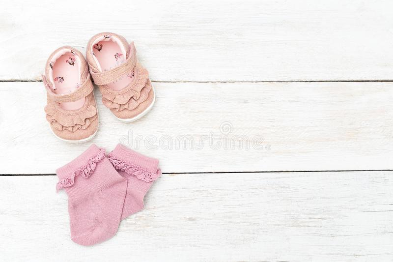 Peúgas e sapatas cor-de-rosa para a menina em um backgroun de madeira branco foto de stock royalty free