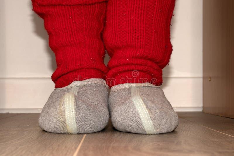 Peúgas feitas malha vermelhas e deslizadores de lã nos pés fotografia de stock royalty free