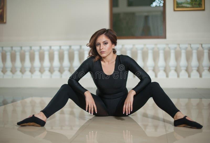 Pełen wdzięku balerina robi rozłamom na marmurowej podłoga Wspaniały baletniczy tancerz wykonuje rozłam na glansowanej podłoga obraz stock