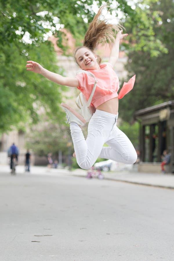 Pełen wigoru i energiczny Energiczny małe dziecko w ruchu na miasto ulicie Skoczny mały dziewczyny doskakiwanie z energicznymi ru zdjęcie stock