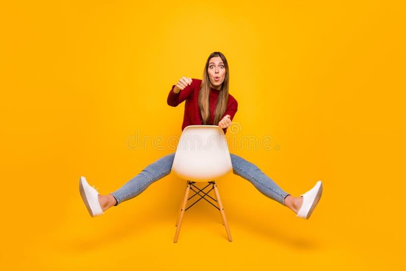 Pełna ciało fotografia damy obsiadania krzesło udaje bieżny pulower odizolowywającego kierowca odzieży żółtego tło zdjęcia royalty free