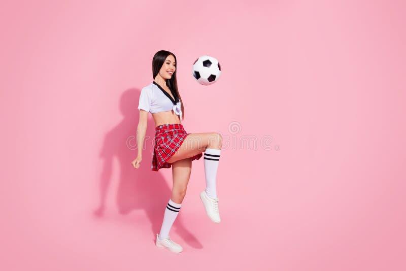 Pełna ciało strony fotografia chłodno damy piłki nożnej piłki gracz robi zadziwiać kantuje nogi odzież czerwona krótka spódnica b fotografia stock