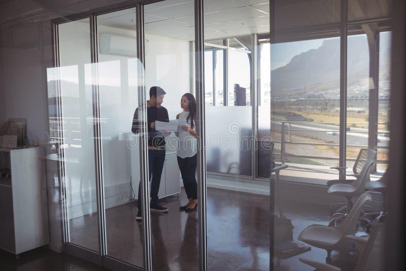 Pełna długość biznesowi koledzy trzyma dokumenty przy biurem obrazy stock