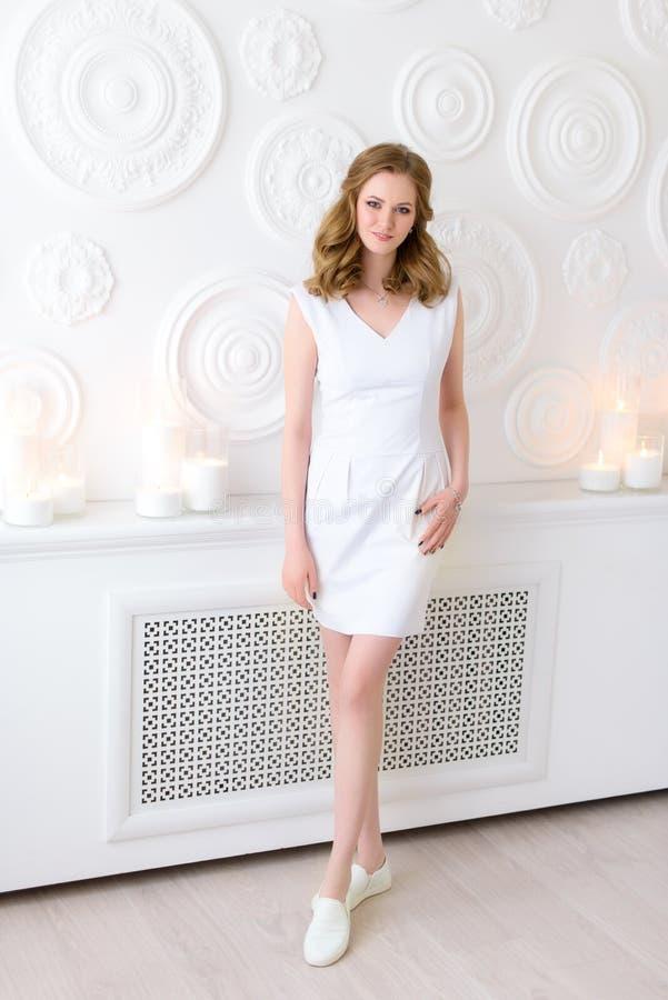 Pełna długość elegancka dziewczyna w uczciwej odzieży i powabnym uśmiechu w całkiem dekorującym pokoju 20 lat mody żeński model obrazy royalty free