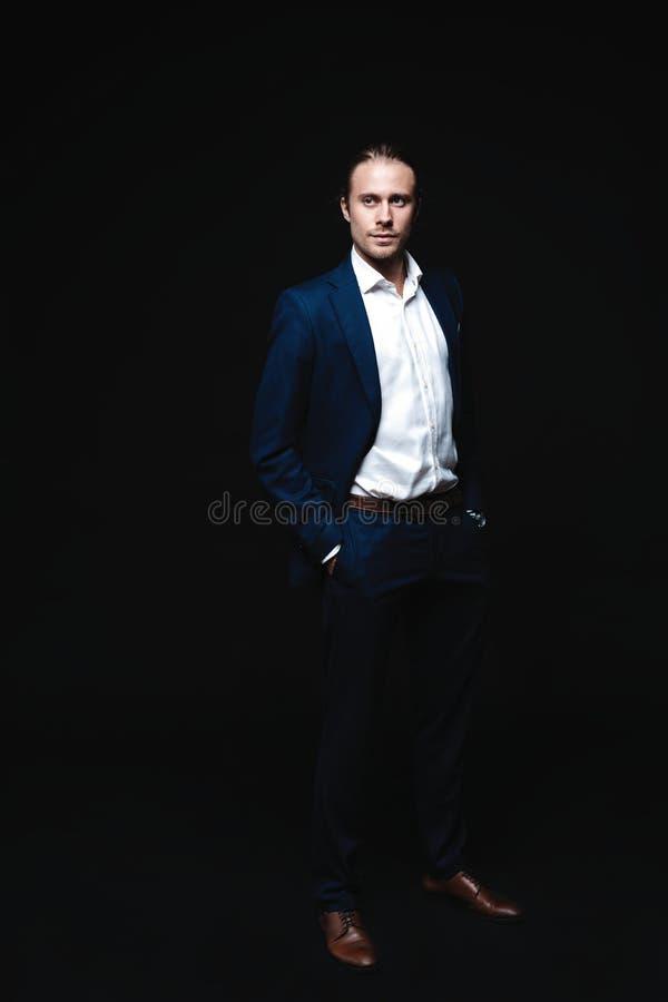 Pełna długość elegancki młody przystojny mężczyzna pozuje w modnym kostiumu, patrzeje kamerę piękny taniec para strzału kobiety p fotografia stock