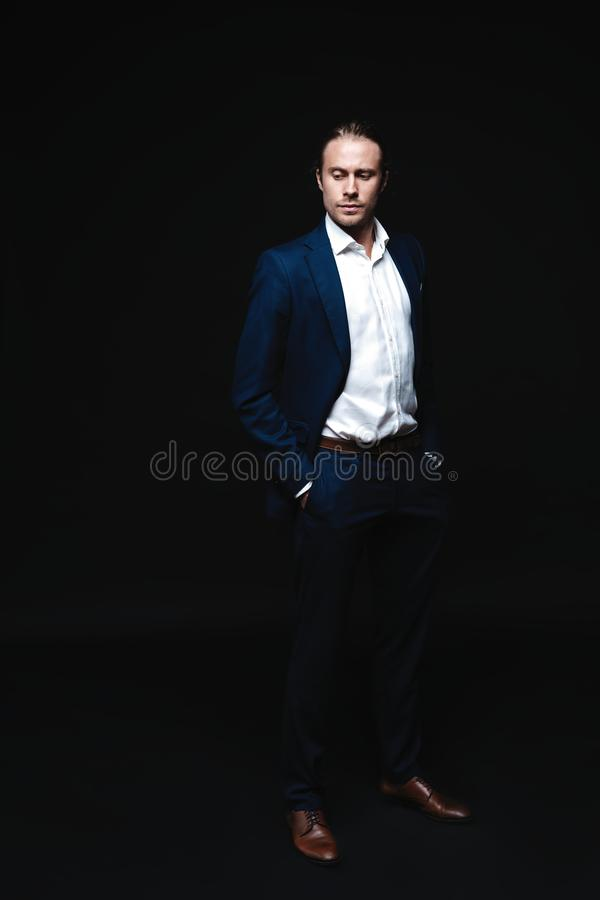 Pełna długość elegancki młody przystojny mężczyzna pozuje w modnym kostiumu, patrzeje kamerę piękny taniec para strzału kobiety p zdjęcia royalty free