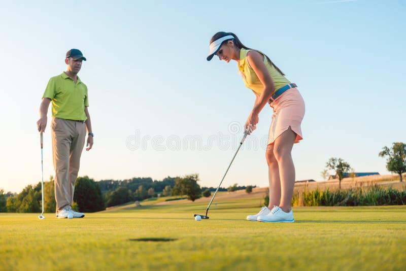 Pełna długość kobieta bawić się fachowego golfa z jej męskim partnerem obrazy stock