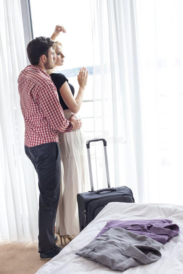 Pełna długość kochający potomstwa dobiera się patrzeć przez okno w pokoju hotelowym obraz stock
