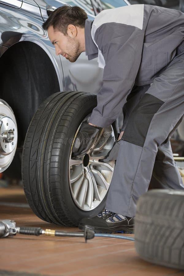 Pełna długość męska mechanika naprawiania samochodu opona w remontowym sklepie obrazy royalty free