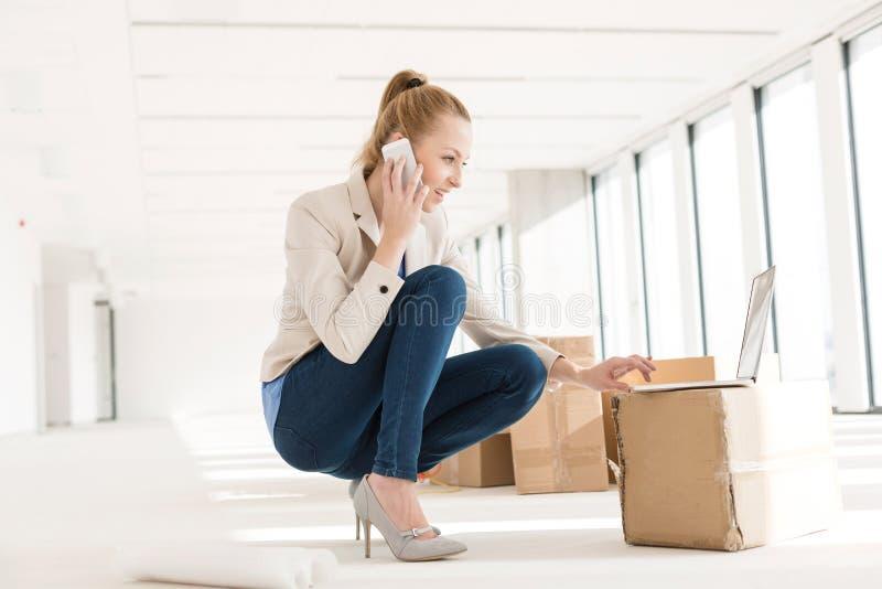 Pełna długość młody bizneswomanu przycupnięcie podczas gdy używać telefon komórkowego i laptop w nowym biurze obraz stock