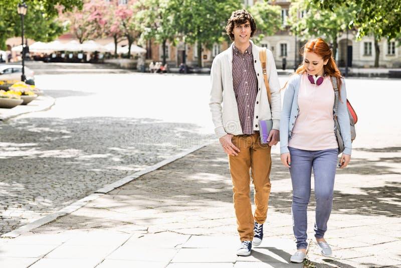Pełna długość młodzi męscy i żeńscy studenci collegu chodzi na footpath obrazy royalty free