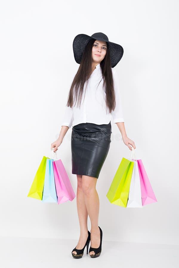 Pełna długość piękna młoda azjatykcia dama w białej bluzce i czarna skóra omijamy trzymać kolorowe torby dziewczyna idzie obrazy stock