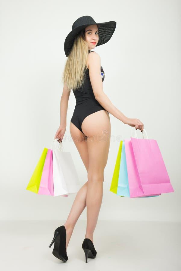 Pełna długość piękna młoda dama w kostiumu kąpielowym, duży czarny kapelusz na szpilkach, trzyma kolorowe torby dziewczyna idzie obraz stock
