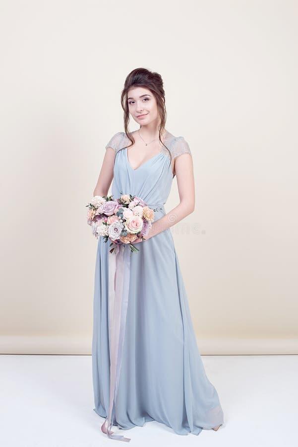 Pełna długość piękny kobieta model trzyma bukiet kwiaty jest ubranym w luksusowej długiej koronkowej sukni odizolowywającej na tl zdjęcie stock