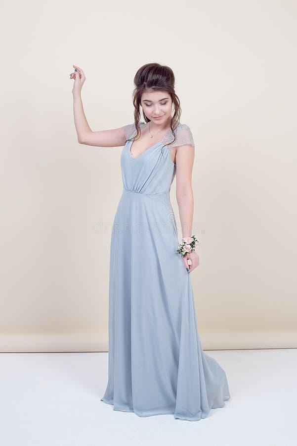 Pełna długość piękny kobieta model trzyma bukiet kwiaty jest ubranym w luksusowej długiej koronkowej sukni odizolowywającej dalej obrazy royalty free