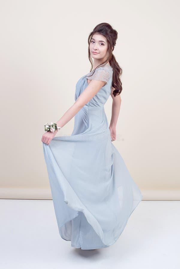 Pełna długość piękny kobieta model trzyma bukiet kwiaty jest ubranym w luksusowej długiej koronkowej sukni odizolowywającej dalej fotografia stock