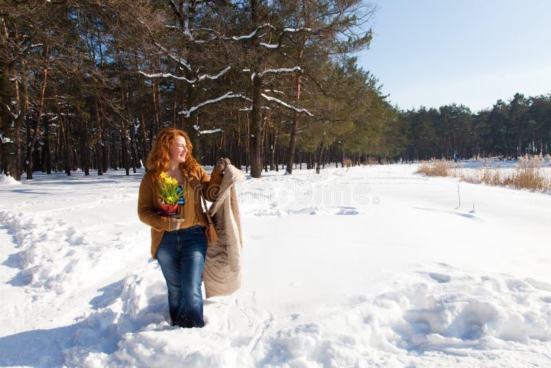 Pełna długość radosna ładna kobieta patrzeje z ukosa i trzyma jej żakiet w ręce z śnieżnymi drzewami na tle obrazy royalty free