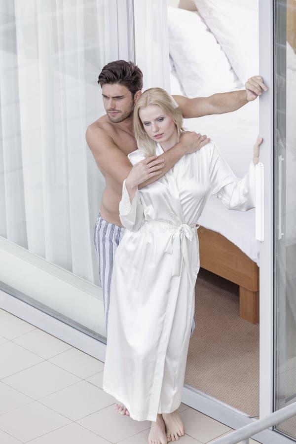 Pełna długość romantyczni potomstwa dobiera się wydatki ilości czas przy balkonowym drzwi zdjęcia royalty free