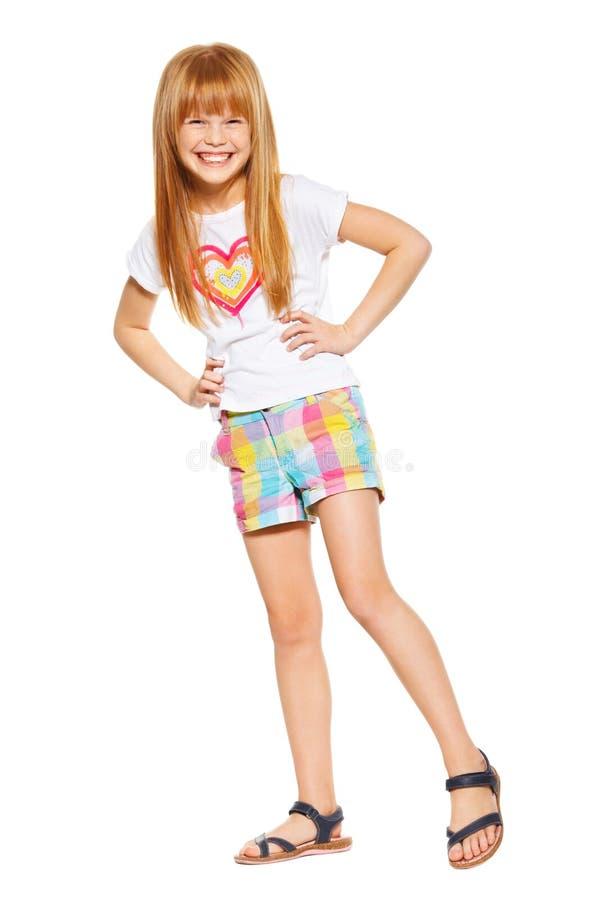 Pełna długość rozochocona mała dziewczynka z czerwonym włosy w skrótach i koszulce; odizolowywający na bielu obrazy stock