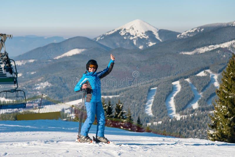 Pełna długość strzelał uśmiechnięta żeńska narciarka pokazuje aprobaty przy zima ośrodkiem narciarskim podczas gdy narciarstwo na fotografia royalty free