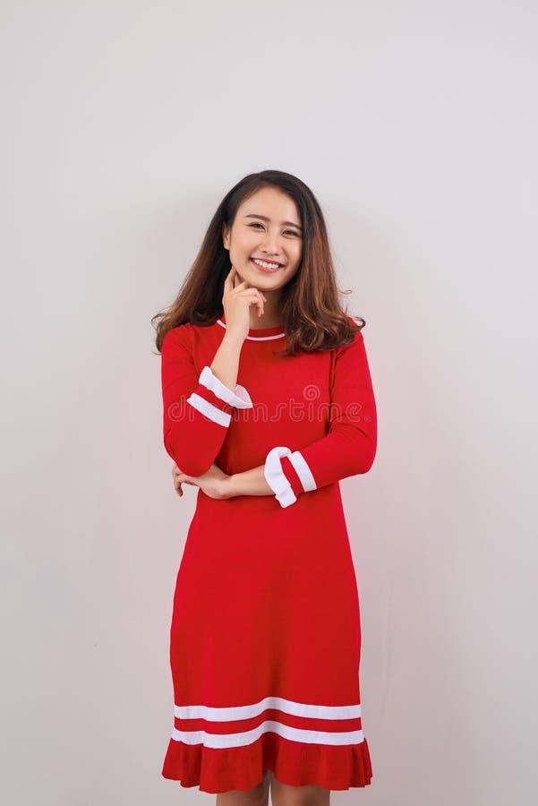 Pełna długość uśmiechnięta figlarnie młoda kobieta stoi nad białym tłem w czerwieni sukni obraz royalty free