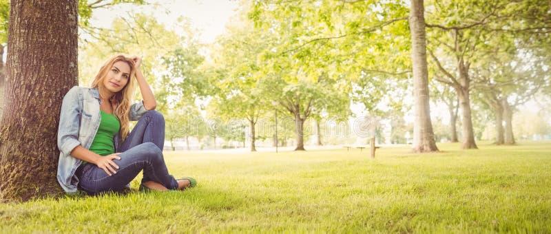 Pełna długość uśmiechnięta kobieta z ręką w włosy podczas gdy siedzący pod drzewem zdjęcia royalty free
