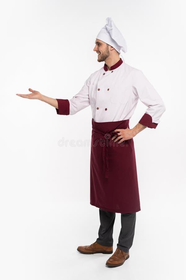 Pełna długość uśmiechnięty potomstwo kucharz w jednolitej pozycji odizolowywającej nad białym tłem Przygl?daj?cy kamery wskazywa? obraz stock